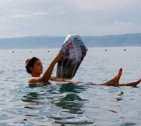 Girl reading newspaper in Dead Sea, Jordan