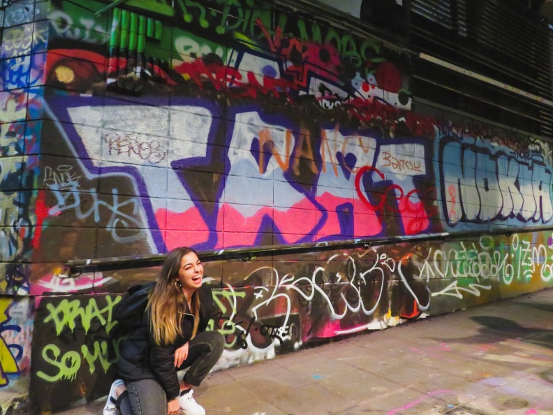 Girl in front of graffiti wall in Leake Street Tunnel, Waterloo, London.